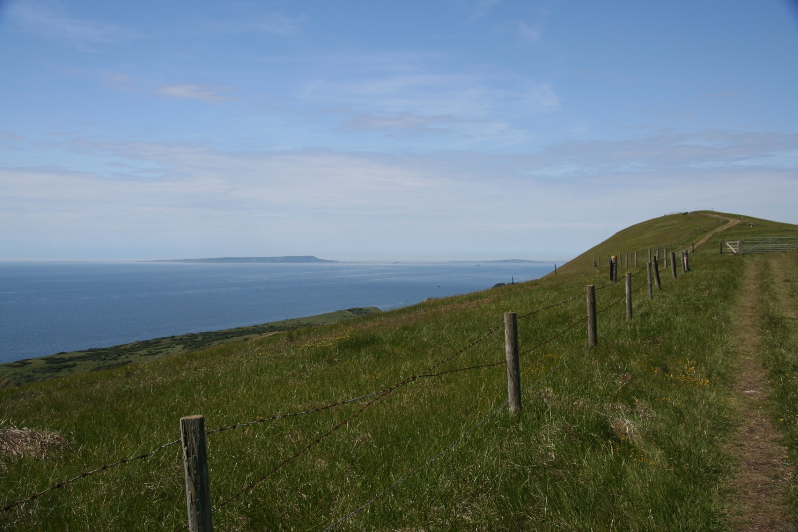 A fairly flat bit of path with Portland beyond.