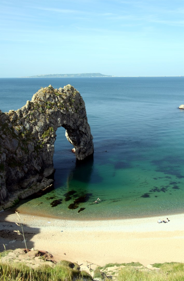 Durdle Door in the morning with Portland in the distance.