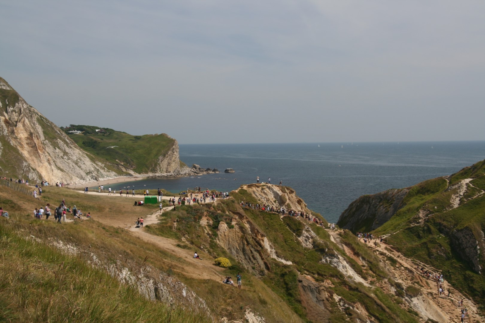 The area around Durdle Door in the summer with a queue down to the beach.